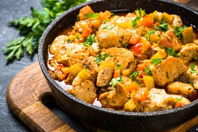 Chicken stew with vegetables black stone table, top view