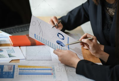 Female accountant team is analyzing data documents in the office