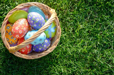 Flat lay shot of Easter eggs in the wicker basket on green sprin