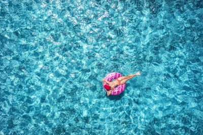 Woman swimming on pink donut swim ring in blue sea. Aerial view