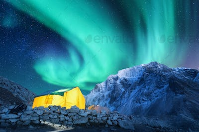 Aurora borealis, yellow glowing tent and snowy mountains