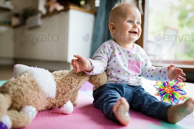 Happy one year old girl sitting with plush toy