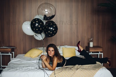 Attractive model lying on bed and holding black and white balloons