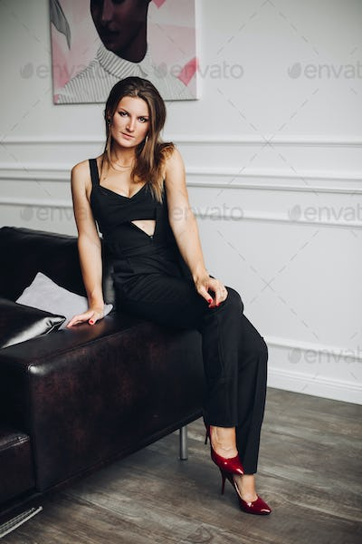 Charming woman in elegant black overall sitting on couch, posing