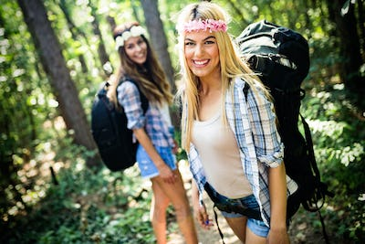 Adventure, travel, tourism, hike and people concept. Happy woman walking with backpacks in woods