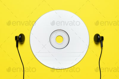 Blank CD and headphones on yellow background