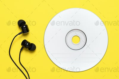 Compact disc and earbuds on yellow background