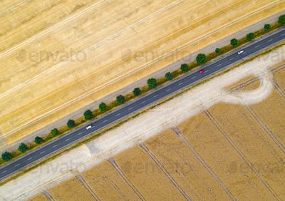 Aerial view of a country road between agricultural fields in Europe