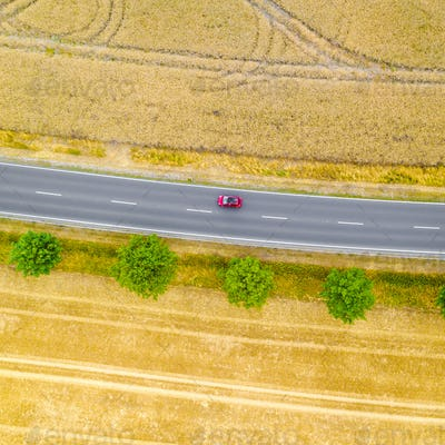 Aerial view of a country road with a red car