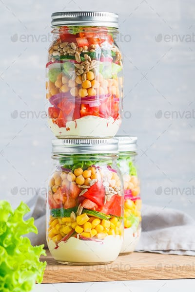 Glass jars with layering vegan salad for healthy lunch. The concept of fitness and vegetarian food.