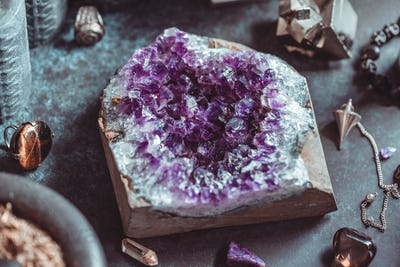 Amethyst Druze on a witch's altar for a magical ceremony among crystals and black candles.