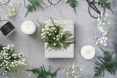 Christmas wrapping gift box among plants and white candles, florist workshop, photo set.