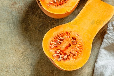 View on raw halves of butternut squash on a kitchen table. Seasonal vegetable food, still life.