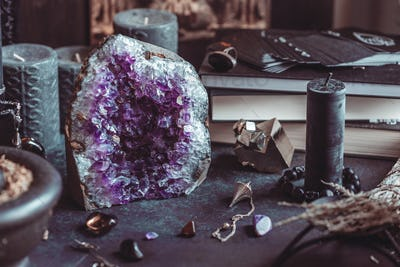 Amethyst Druze on a witch's altar for a magical ritual among crystals and black candles.