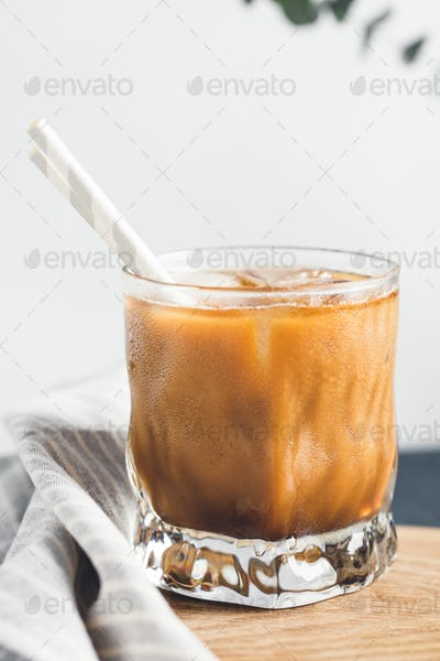 Ice latte in a glass with straws in on a wooden board in a kitchen.