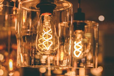 Close up view on a transparent modern lamp with a retro bulb inside it.