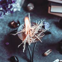 Burning herbs on a witch's altar for a magical ritual among crystals and black candles.