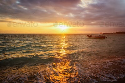 Calm ocean with boat on sunrise