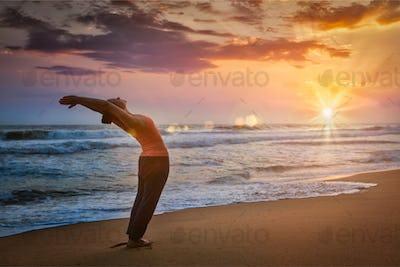 Young sporty fit woman doing yoga Sun salutation Surya Namaskar