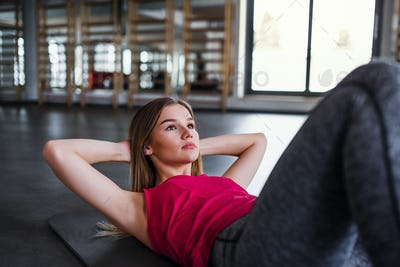 A portrait of young girl or woman doing exercise in a gym.