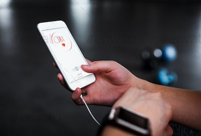 A midsection of woman with smartphone in a gym, checking heart rate.