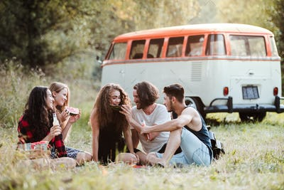 A group of friends sitting on ground on a roadtrip through countryside, having picnic.