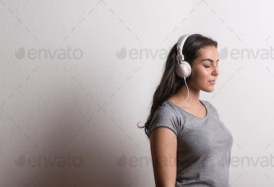 Young beautiful happy woman with headphones in studio, eyes closed. Copy space.