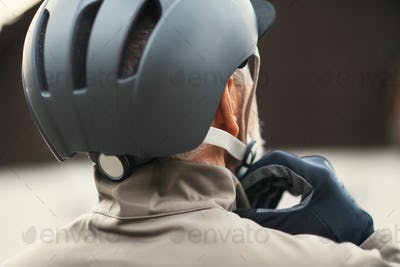 A rear view of active senior man standing outdoors in town, putting on a bike helmet.