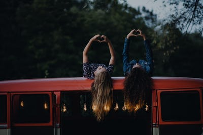 Two girl friends at dusk outdoors on a roadtrip through countryside, having fun.