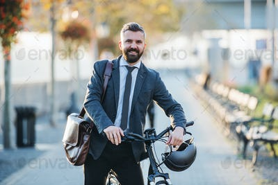 Businessman commuter with bicycle walking home from work in city.