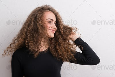 Young beautiful happy woman standing in studio.
