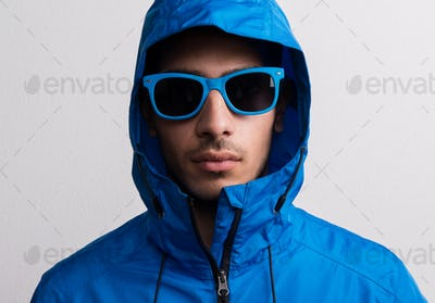 Portrait of a young serious hispanic man with blue sunglasses and anorak in a studio.