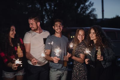 A group of friends with sparkles standing outdoors at dusk.
