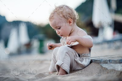 A small toddler girl sitting on beach on summer holiday.