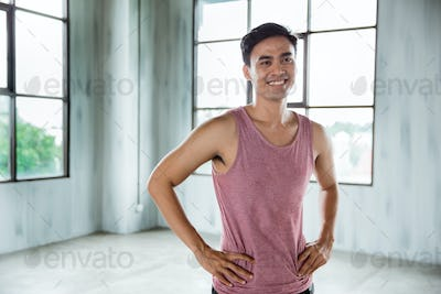 asian sport man smiling and his hands on hips