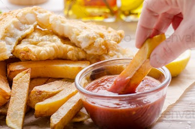 Traditional British street food fish and chips with ketchup sauc