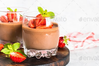 Chocolate dessert of whipped cream and strawberries in glass