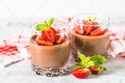 Chocolate panna cotta sweet dessert with strawberries in glass