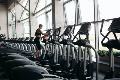 Young attractive fitness woman running on treadmill at panoramic window