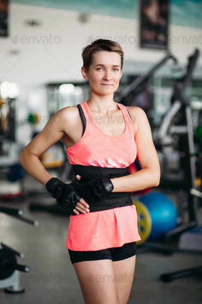 Serious sporty woman with strong body, wearing in pink t-shirt posing, looking at camera. Young