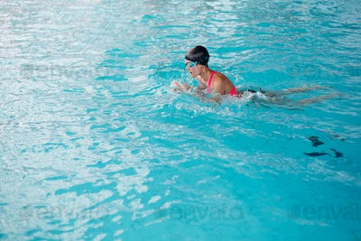 Side view of girl in goggles in the blue water pool