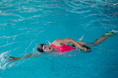 Female in pink swimwear swimming in blue water pool