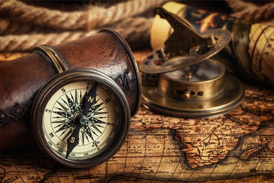Old vintage compass on ancient map