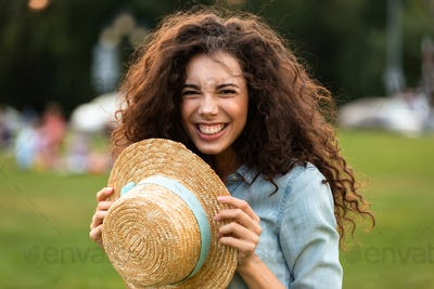 Image of beautiful woman 20s holding straw hat and laughing, whi