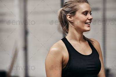 Fit young woman standing in a gym smiling