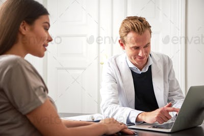 Cheerful beautician pointing at laptop consulting young woman
