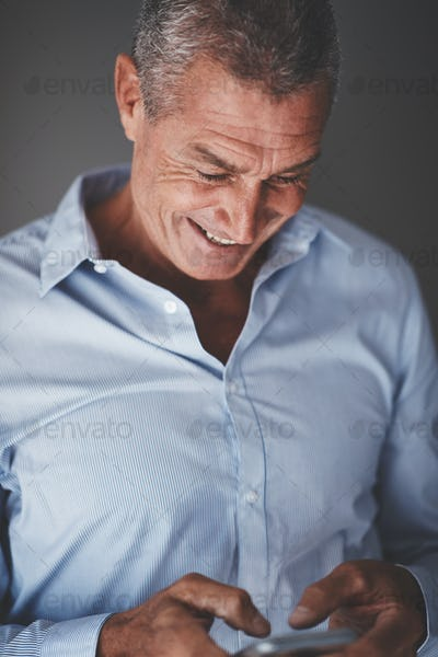 Smiling mature businesman standing against a gray background reading texts