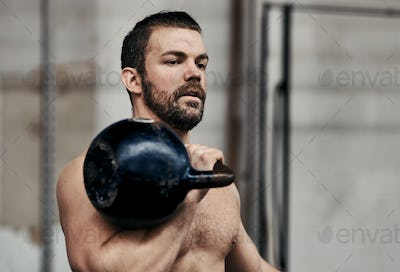 Fit young man lifting a dumbbell while working out