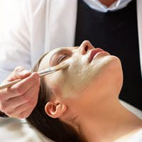 Cosmetologist putting mask on female face with brush in salon