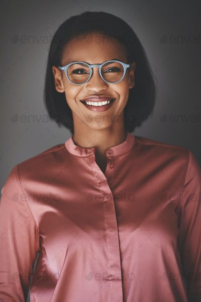 Young African businesswoman smiling confidently against a gray background